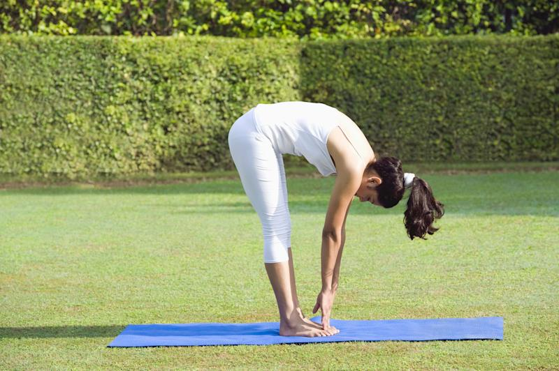 """A forward bend provides a soothing feeling of release -- making the pose <a href=""""http://www.huffingtonpost.com/2013/05/19/yoga-for-anxiety-10-poses_n_3281986.html"""" target=""""_blank"""">therapeutic for stress and anxiety</a> -- and with the added arm bind, this standing forward bend variation provides a deep shoulder stretch as well. Stand with your feet at hips-width distance, and slowly bend forward from the hips to come into the forward bend. To take the strain off the lower back, bend the knees slightly. Then, try adding an arm bind to stretch the shoulders: Interlace your hands at the lower back and stretch the arms over your head and hands towards the ground in front of you. For those with tight shoulders, hold a belt between your hands, allowing the shoulders to get a deep but less intense stretch. """"By binding the hands, you also allow the arms to stretch and tight shoulders to relax,"""" Bielkus says. """"After sitting all day, it's a great idea to turn your world upside down and bring some blood back to the brain while getting a great stretch for the legs."""""""