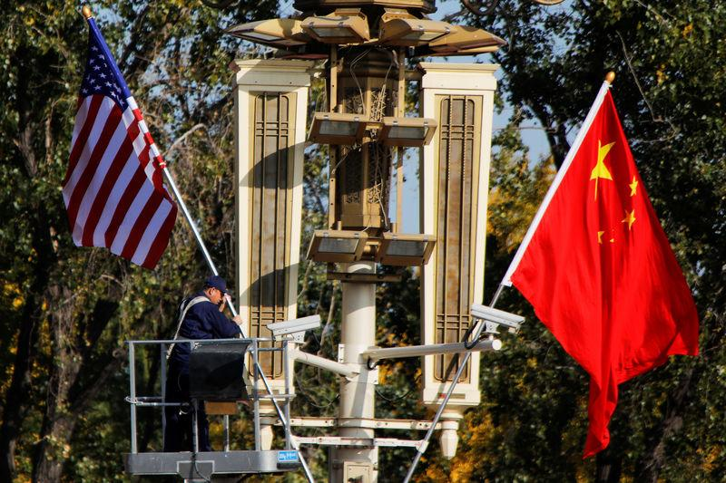 FILE PHOTO: A worker places U.S. and China flags near the Forbidden City ahead of a visit by U.S. President Donald Trump to Beijing, in Beijing