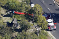 A crane is used to lift a vehicle following a rollover accident involving golfer Tiger Woods, Tuesday, Feb. 23, 2021, in Rancho Palos Verdes, Calif., a suburb of Los Angeles. Woods suffered leg injuries in the one-car accident and was undergoing surgery, authorities and his manager said. (AP Photo/Mark J. Terrill)