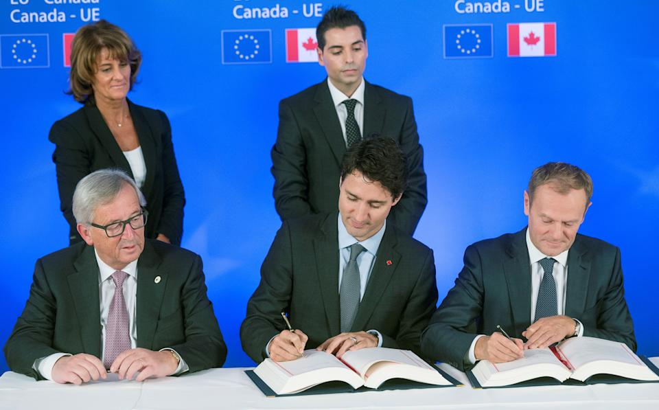 (From L) President of the European Commission Jean-Claude Juncker looks on as Canada's Prime Minister Justin Trudeau (C) and European Council President Donald Tusk sign the Comprehensive Economic and Trade Agreement (CETA), at the European Council in Brussels, on October 30, 2016. Canadian Prime Minister Justin Trudeau and European Union leaders on October 30, 2016 finally signed a landmark trade deal seven years in the making, after it was nearly being torpedoed by a small region of Belgium. CETA removes 99 percent of customs duties between the two sides, linking the single EU market with the world's 10th largest economy. / AFP / POOL / Thierry MONASSE        (Photo credit should read THIERRY MONASSE/AFP via Getty Images)