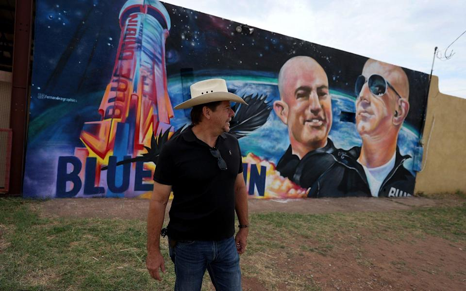 David Morales stands near a mural on the side of his building he had painted to honor Jeff Bezos as the billionaire plans to launch his Blue Origin rocket from a launchpad in West Texas - Joe Raedle/Getty Images North America