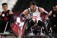 Joshua Wheeler of the United States carries a ball against Canada's defense during a Pool Phase Group match of Wheelchair Rugby at the Tokyo 2020 Paralympic Games, Thursday, Aug. 26, 2021, in Tokyo, Japan. (AP Photo/Shuji Kajiyama)