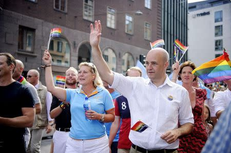 Swedish Prime Minister Fredrik Reinfeldt and Energy Minister Catharina Elmsater-Svard head the government section of the annual gay pride parade in Stockholm