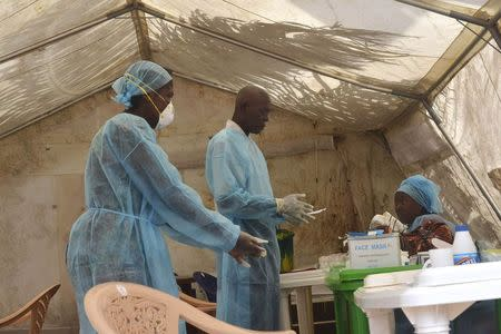 Health workers take blood samples for Ebola virus testing at a screening tent in the local government hospital in Kenema