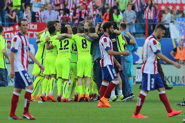 Atletico players walk off the field as Barcelona's players celebrate winning the championship and the game at the Vicente Calderon stadium in Madrid on May 17, 2015 (AFP Photo/Cesar Manso)