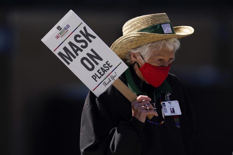 FILE - In this March 16, 2021, file photo, an usher holds a sign to remind fans to wear masks during a spring training baseball game between the Oakland Athletics and the Arizona Diamondbacks in Scottdale, Ariz. Arizona on Friday, Aug. 27, 2021, surpassed the milestone of 1 million confirmed coronavirus cases after the state reported 3,707 new infections amid continued wrangling over vaccinations and mask requirements. (AP Photo/Ashley Landis, File)