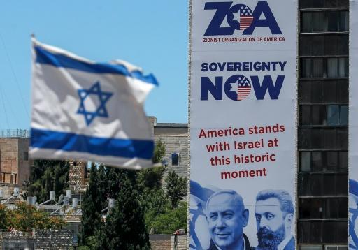 A banner in Jerusalem of the Zionist Organisation Of America, next to an Israeli flag, pledges support for Israel's plan to annex parts of the occupied West Bank