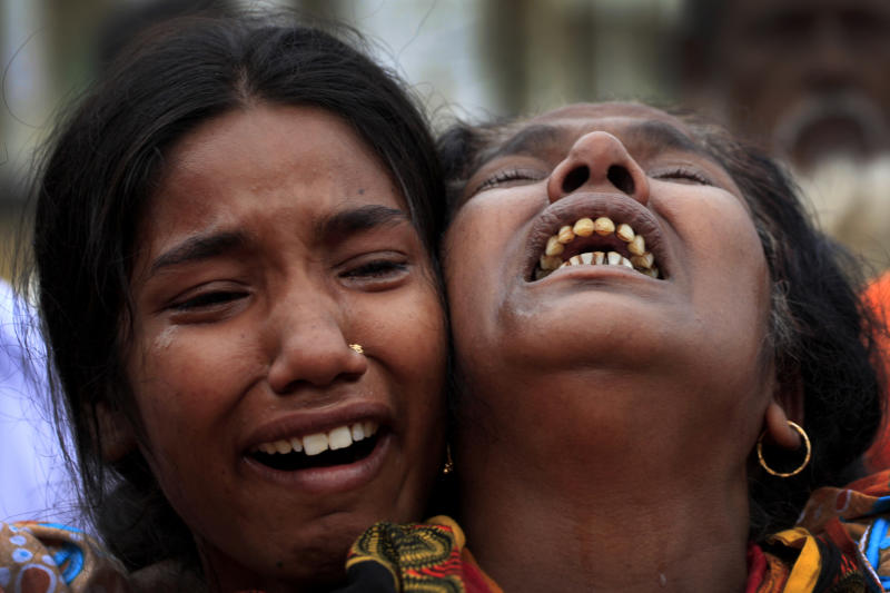 A woman is comforted as she grieves after identifying the body of her daughter, a victim of the garment factory collapse, Sunday, May 5, 2013 in Savar, near Dhaka, Bangladesh. The death toll from the collapse of a shoddily built garment-factory building in Bangladesh continued its horrifying climb, reaching 580 on Sunday with little sign of what the final number will be. The disaster is likely the worst garment-factory accident ever, and there have been few industrial accidents of any kind with a higher death toll. (AP Photo/Wong Maye-E)