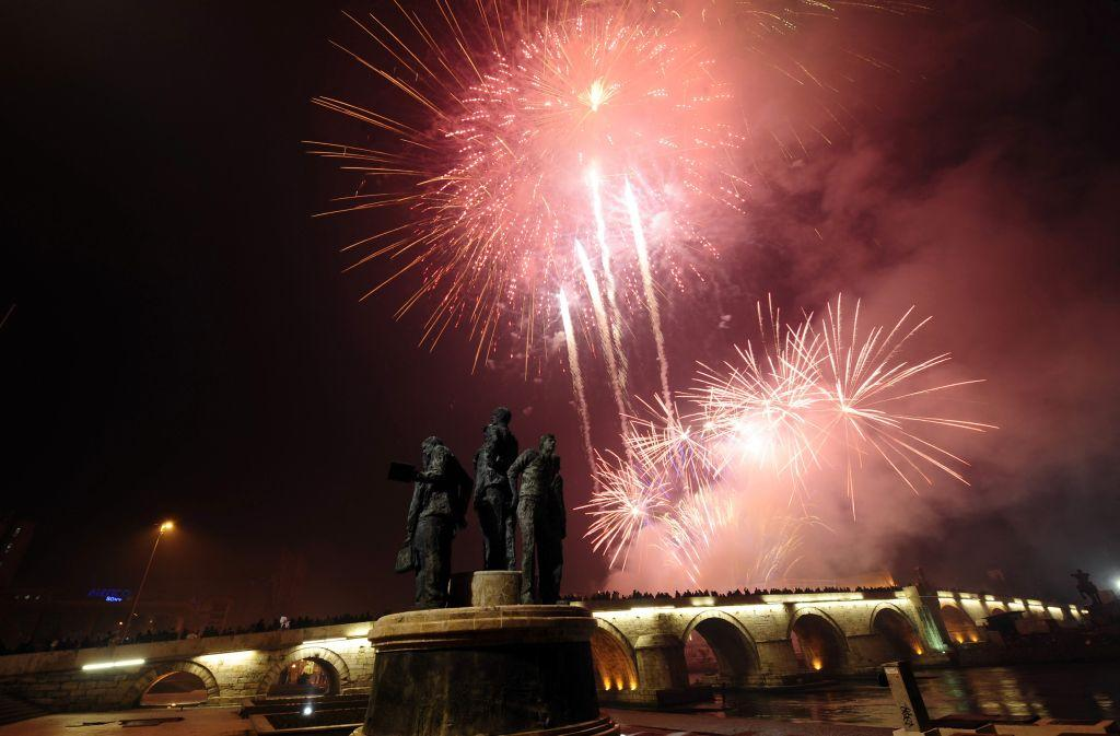 Residents watch as fireworks explode over the Stone Bridge during New Year celebrations in Skopje January 1, 2013.