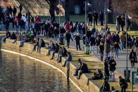 People with and without face mask sit and walk at the river Main in Frankfurt, Germany, on a sunny Saturday, March 6, 2021. (AP Photo/Michael Probst)