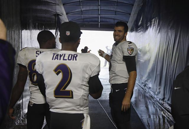 Baltimore Ravens quarterback Joe Flacco (5) watches the severe storm passing through the area from inside the tunnel with Torrey Smith and Tyrod Taylor (2) during the first half of an NFL football game against the Chicago Bears, Sunday, Nov. 17, 2013, in Chicago. Play was suspended in the game. (AP Photo/Charles Rex Arbogast)