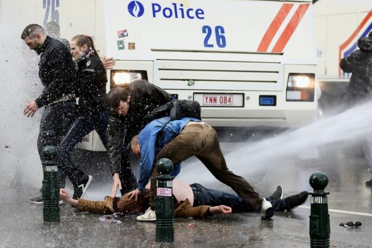 Fellow protesters try to help an injured man even as he is being hit by a police water cannon at the banned park party in Brussels