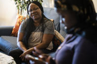 Rebecca Williams Sonyah, left, watches her daughter Fatumata Kromah, right, browse social media during an interview at her home, Thursday, April 22, 2021, in Brooklyn Center. When protests began in a Minneapolis suburb after a white police officer fatally shot a Black man, 21-year-old Fatumata Kromah took to the street, pushing for change she says is essential to her Liberian immigrant community. (AP Photo/John Minchillo)