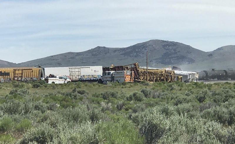 In this photo provided by the Nevada Department of Public Safety is a train derailment Wednesday, June 19, 2019, near Wells, Nev. A train carrying military munitions derailed in the high desert of northeast Nevada on Wednesday, closing an interstate for about an hour before emergency crews determined there was no danger. No injuries were reported. Officials say cars carrying the munitions to a Nevada Army depot were not among those that derailed near the community of Wells not far from the Utah-Nevada state line. (Nevada Department of Public Safety via AP)