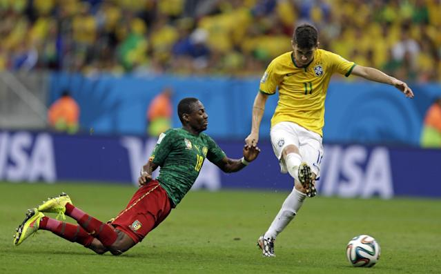 Cameroon's Eyong Enoh, left, falls beside Brazil's Oscar during the group A World Cup soccer match between Cameroon and Brazil at the Estadio Nacional in Brasilia, Brazil, Monday, June 23, 2014. (AP Photo/Andre Penner)
