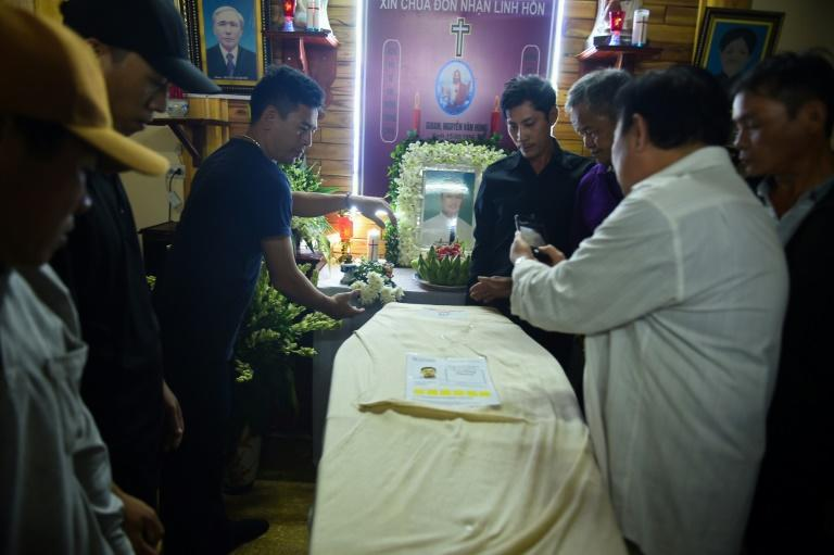 Relatives place the casket bearing the body of Nguyen Van Hung at his home in Dien Chau district, Vietnam