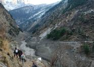 People walk past a destroyed dam after a Himalayan glacier broke and crashed into the dam at Raini Chak Lata