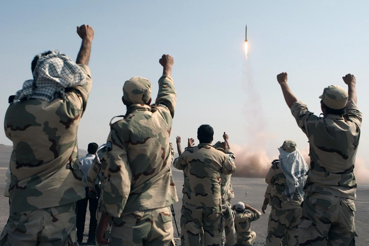 In this photo released by the Islamic Republic News Agency (IRNA), members of the Iranian Revolutionary Guard celebrate after launching a missile during their maneuver in an undisclosed location in Iran, Tuesday, July 3, 2012. Iran's powerful Revolutionary Guards test fired several ballistic missiles on Tuesday, including a long-range variety capable of hitting U.S. bases in the region as well as Israel, Iranian media reported. (AP Photo/IRNA, Mostafa Qotbi)