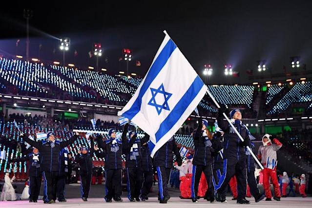 <p>Flag bearer Alexei Bychenko of Israel and teammates enter the stadium wearing navy winter apparel featuring cobalt blue stripes along their pants and jacket zippers during the opening ceremony of the 2018 PyeongChang Games. (Photo: Matthias Hangst/Getty Images) </p>