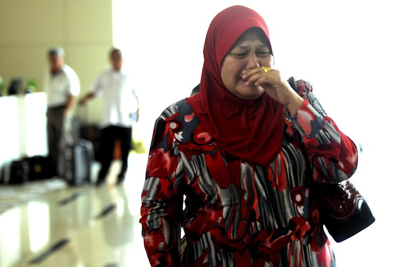 A relative cries as she arrives at a hotel designated as a holding area for family members of passengers on board the missing Malaysia Airlines jetliner MH370, Wednesday, March 12, 2014, in Sepang, Malaysia. More than four days after a Malaysian jetliner went missing on route to Beijing, authorities acknowledged Wednesday they didn't know in which direction the plane and its 239 passengers was heading when it disappeared, vastly complicating efforts to find it. (AP Photo/Joshua Paul)