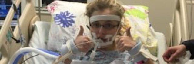 The author in a hospital bed with her thumbs up