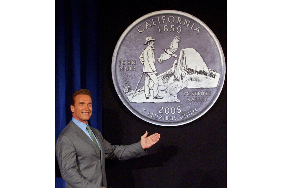 FILE - Then-California Gov. Arnold Schwarzenegger displays the final choice for the California commemorative quarter, featuring an image of naturalist John Muir, in Sacramento, Calif., on March 29, 2004. The Sierra Club is reckoning with the racist views of founder John Muir, the naturalist who helped spawn environmentalism. The San Francisco-based environmental group said Wednesday, July 22, 2020 that Muir was part of the group's history perpetuating white supremacy. (AP Photo/Rich Pedroncelli, File)