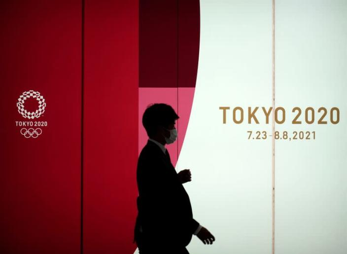 A man wearing a protective face mask walks by an advertising of Tokyo 2020 Olympic Games