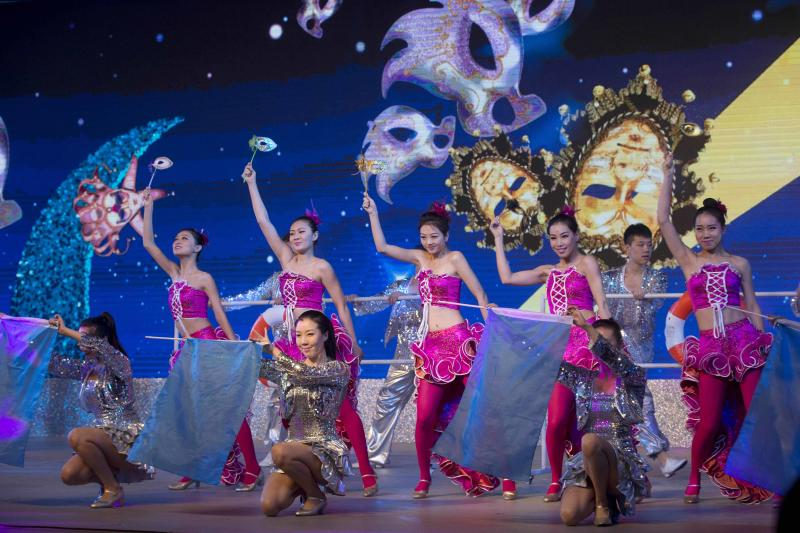 Dancers perform during a Dalian Wanda Group event at a hotel in Beijing, China, Wednesday, June 19, 2013. Chinese property and cinema conglomerate Dalian Wanda Group said it is buying British yacht maker Sunseeker and will develop an upmarket London hotel, expanding into the luxury market as part of the latest foray abroad by a major Chinese firm. (AP Photo/Ng Han Guan)
