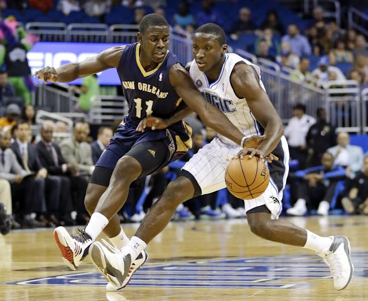 New Orleans Pelicans' Jrue Holiday (11) tries to steal the ball as Orlando Magic's Victor Oladipo drives to the basket during the first half of an NBA preseason basketball game in Orlando, Fla., Friday, Oct. 25, 2013. AP Photo/John Raoux)
