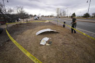 People look over debris that fell off a plane that shed parts over a neighborhood in Broomfield, Colo., Saturday, Feb. 20, 2021. The plane was making an emergency landing at nearby Denver International Airport. (AP Photo/David Zalubowski)