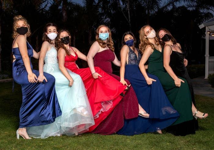 Modern teen girls wearing masks and brightly colored modern dresses