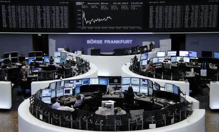 Traders are pictured at their desks in front of the DAX board at the Frankfurt stock exchange May 29, 2014. REUTERS/Remote/Stringer