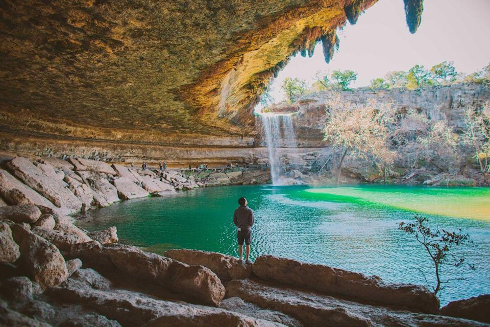 """<p>Just a 45-minute drive outside of Austin, the cave formations of the <a href=""""https://parks.traviscountytx.gov/parks/hamilton-pool-preserve"""" rel=""""nofollow noopener"""" target=""""_blank"""" data-ylk=""""slk:Hamilton Pool Preserve"""" class=""""link rapid-noclick-resp"""">Hamilton Pool Preserve</a> have become a """"watering hole"""" for <a href=""""https://www.bestproducts.com/parenting/g32894824/durable-kids-hiking-boots/"""" rel=""""nofollow noopener"""" target=""""_blank"""" data-ylk=""""slk:hikers"""" class=""""link rapid-noclick-resp"""">hikers</a> and swimmers looking to escape the city. </p><p>The water is crystal clear where you'll be able to easily find fish and other creatures. The formations of this preserve were created from the collapse of a cave into Hamilton Creek, with huge limestone cliffs surrounding the pool. Visitors can even walk under a 50-foot waterfall!</p>"""