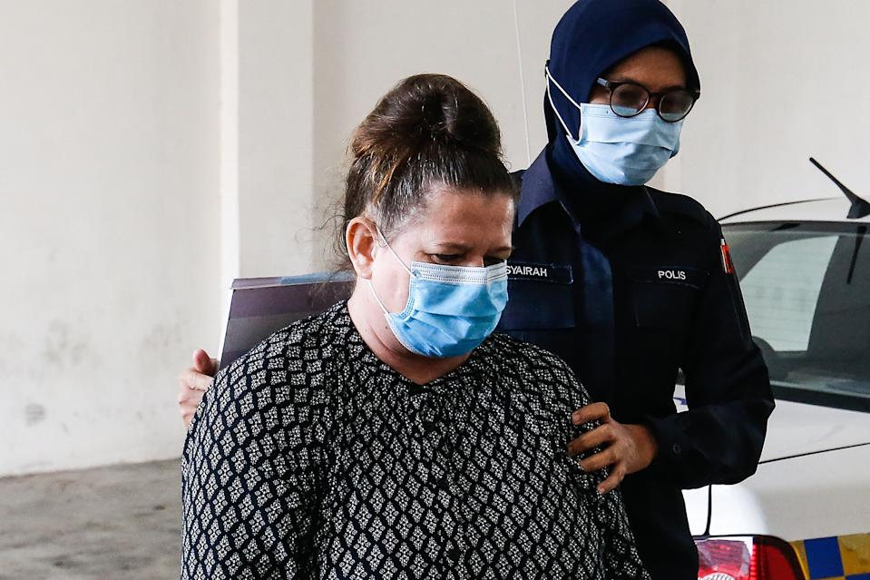 British national Samantha Jones (L), accused of killing her husband in 2018, is escorted by a police officer as she arrives at a court in Alor Setar, in northern Malaysia, on August 3, 2020. - Jones was arrested two years ago after her husband John William Jones was found with a stab wound to his chest in his house on the Malaysian holiday island of Langkawi. (Photo by A. Ammarudin / AFP) (Photo by A. AMMARUDIN/AFP via Getty Images)