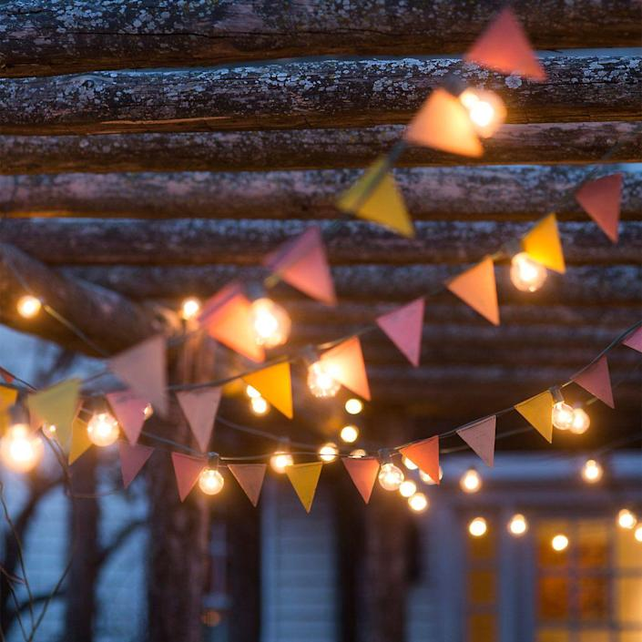 """<p>Mix string lights with colorful bunting for a layered lit-up look.</p><p><strong>See more at <a href=""""https://www.shopterrain.com/products/led-globe-lights"""" rel=""""nofollow noopener"""" target=""""_blank"""" data-ylk=""""slk:Terrain"""" class=""""link rapid-noclick-resp"""">Terrain</a>.</strong></p><p><strong><a class=""""link rapid-noclick-resp"""" href=""""https://www.amazon.com/YGEOMER-Colorful-Pennants-Multicolor-Celebrations/dp/B073GVW5VL/ref=sr_1_3?tag=syn-yahoo-20&ascsubtag=%5Bartid%7C10050.g.3404%5Bsrc%7Cyahoo-us"""" rel=""""nofollow noopener"""" target=""""_blank"""" data-ylk=""""slk:Shop bunting flags"""">Shop bunting flags</a></strong></p>"""
