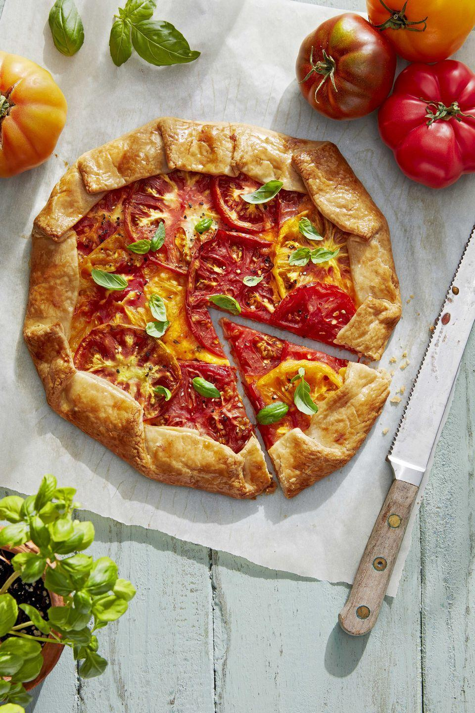 """<p>Celebrate summer's favorite fruit (yes, tomatoes are a fruit) in a cheesy galette all rolled up in a store-bought crust.<a href=""""https://www.countryliving.com/food-drinks/a28608360/rustic-tomato-galette-recipe/"""" rel=""""nofollow noopener"""" target=""""_blank"""" data-ylk=""""slk:"""" class=""""link rapid-noclick-resp""""><br></a></p><p><strong><a href=""""https://www.countryliving.com/food-drinks/a28608360/rustic-tomato-galette-recipe/"""" rel=""""nofollow noopener"""" target=""""_blank"""" data-ylk=""""slk:Get the recipe"""" class=""""link rapid-noclick-resp"""">Get the recipe</a>.</strong> <br></p>"""