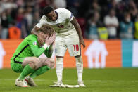 England's Raheem Sterling comforts England's goalkeeper Jordan Pickford after the penalty shootout of the Euro 2020 soccer championship final between England and Italy at Wembley stadium in London, Sunday, July 11, 2021. (AP Photo/Frank Augstein, Pool)