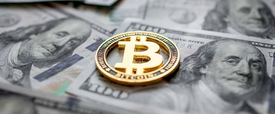 Golden symbolic coin Bitcoin on banknotes of one hundred dollars.