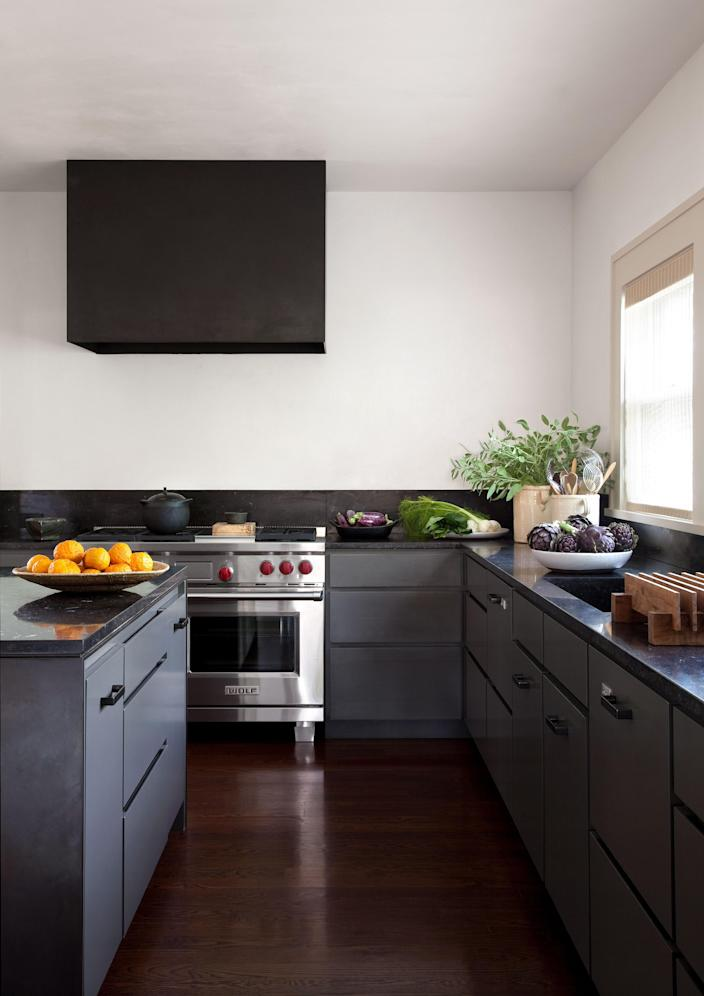 """<div class=""""caption""""> In keeping with Tedhams's reliance on a limited palette, the kitchen cabinets are painted the same color as the exterior of the house. Countertops are Belgian bluestone. Range by <a href=""""https://www.subzero-wolf.com/"""" rel=""""nofollow noopener"""" target=""""_blank"""" data-ylk=""""slk:Wolf"""" class=""""link rapid-noclick-resp"""">Wolf</a>; dishwasher by <a href=""""https://www.fisherpaykel.com/us/"""" rel=""""nofollow noopener"""" target=""""_blank"""" data-ylk=""""slk:Fisher & Paykel"""" class=""""link rapid-noclick-resp"""">Fisher & Paykel</a>. </div>"""
