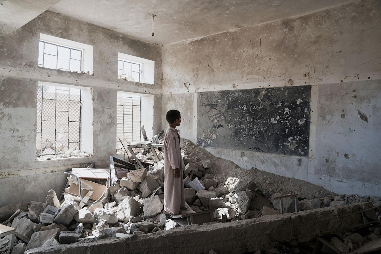 <p>Aal Okab School, Saada City, Yemen, April 24, 2017: A student at the Aal Okab school stands in the ruins of one of his former classrooms, which was destroyed during the conflict in June 2015. Students now attend lesson in UNICEF tents nearby. (Photograph by Giles Clarke for UN OCHA/Getty Images) </p>