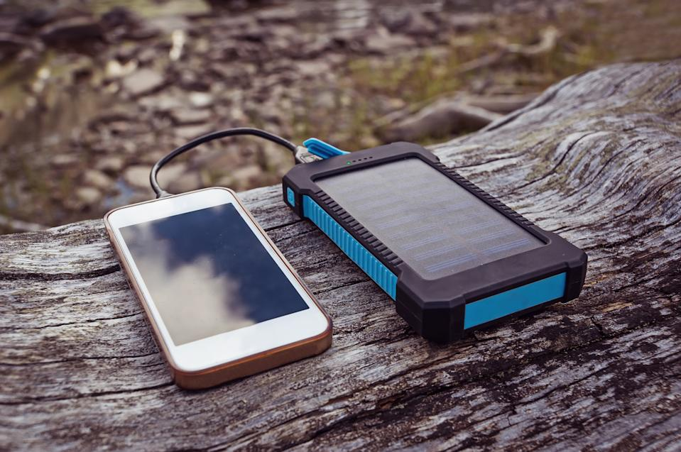 solar power bank charging smart phone lying on a log