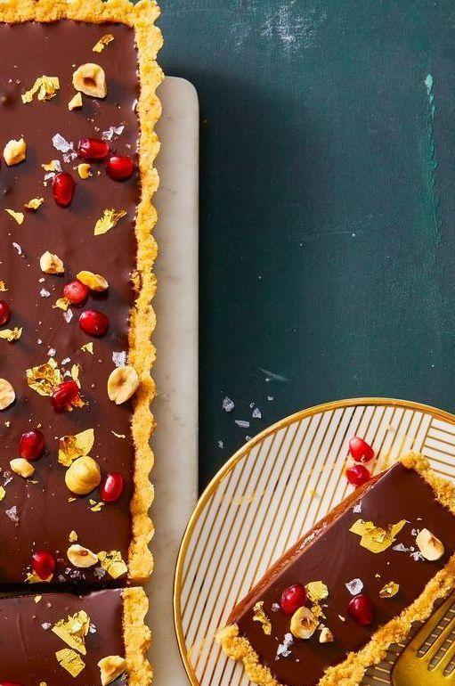 "<p>Layer gooey caramel and rich chocolate ganache into a hazelnut crust for a celebratory sweet everyone will love.</p><p><em><a href=""https://www.goodhousekeeping.com/food-recipes/a29658256/chocolate-hazelnut-and-caramel-tart-recipe/"" rel=""nofollow noopener"" target=""_blank"" data-ylk=""slk:Get the recipe for Chocolate, Hazelnut & Caramel Tart »"" class=""link rapid-noclick-resp"">Get the recipe for Chocolate, Hazelnut & Caramel Tart »</a></em></p>"