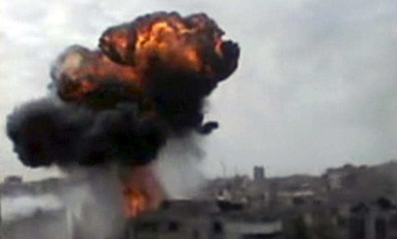 In this image made from amateur video released by the Shaam News Network and accessed Sunday, April 15, 2012, smoke billows an impact following purported shelling in Homs, Syria. Syrian troops are reported to have shelled residential neighborhoods dominated by rebels in the central city of Homs Sunday, activists said, killing at least three people hours before the first batch of United Nations observers were to arrive in Damascus to shore up a shaky truce. (AP Photo/Shaam News Network via AP video) TV OUT, THE ASSOCIATED PRESS CANNOT INDEPENDENTLY VERIFY THE CONTENT, DATE, LOCATION OR AUTHENTICITY OF THIS MATERIAL