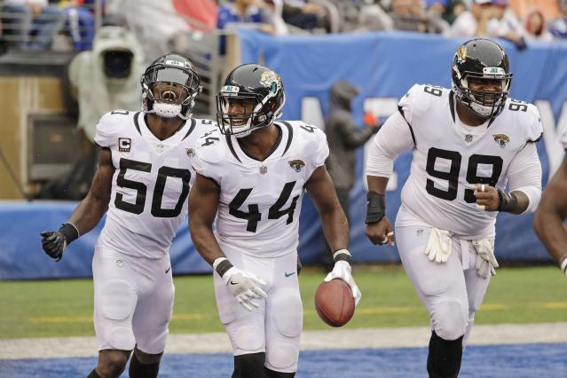 Jacksonville Jaguars' Myles Jack (44) celebrates with teammtes Telvin Smith (50) and Marcell Dareus (99) after returning an interception for a touchdown during the second half of an NFL football game against the New York Giants Sunday, Sept. 9, 2018, in East Rutherford, N.J. The Jaguars won 20-15. (AP Photo/Seth Wenig)