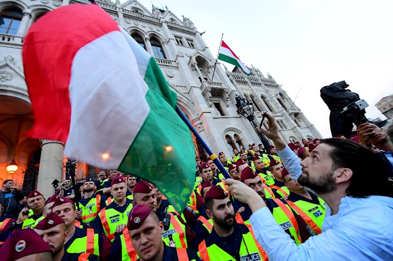 People protest as police officers stand guard in front of the parliament building in Budapest on April 4, 2017
