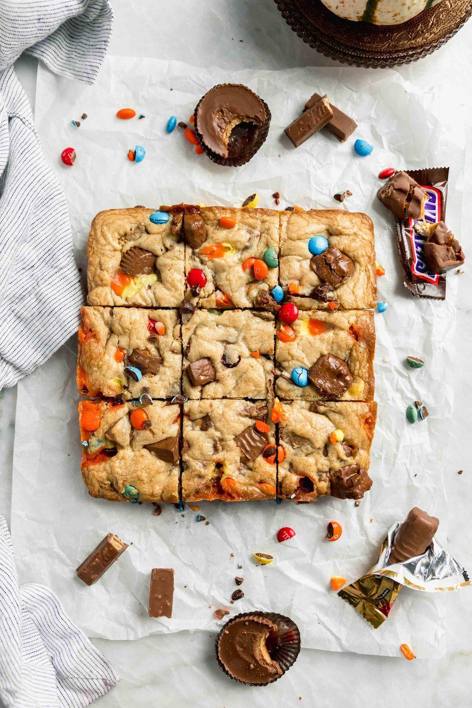 """<p>You can use nearly any type of chocolate candy in this recipe: Chocolate bars, M&Ms, and candy corn are all fair game. Just chop each one into bite-sized pieces and throw it on in.</p><p><strong>Get the recipe at <a href=""""https://bromabakery.com/halloween-candy-cookie-bars/"""" rel=""""nofollow noopener"""" target=""""_blank"""" data-ylk=""""slk:Broma Bakery"""" class=""""link rapid-noclick-resp"""">Broma Bakery</a>.</strong></p><p><a class=""""link rapid-noclick-resp"""" href=""""https://go.redirectingat.com?id=74968X1596630&url=https%3A%2F%2Fwww.walmart.com%2Fip%2FThe-Pioneer-Woman-Spring-Bouquet-2-Piece-Baker-Set%2F595449072&sref=https%3A%2F%2Fwww.thepioneerwoman.com%2Ffood-cooking%2Fmeals-menus%2Fg32110899%2Fbest-halloween-desserts%2F"""" rel=""""nofollow noopener"""" target=""""_blank"""" data-ylk=""""slk:SHOP BAKING PANS"""">SHOP BAKING PANS</a></p>"""