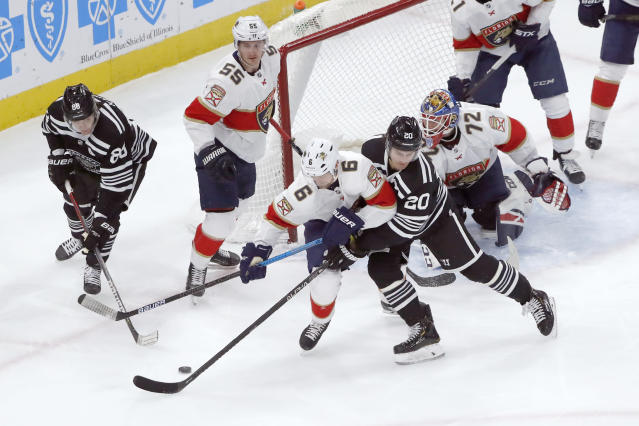 Florida Panthers' Anton Stralman (6) and Chicago Blackhawks' Brandon Saad (20) battle for a loose puck during the first period of an NHL hockey game Tuesday, Jan. 21, 2020, in Chicago. (AP Photo/Charles Rex Arbogast)