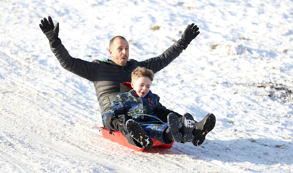 Dave Armitage with son Brodie enjoy sledging in the snow at Tatton Park, Knutsford. (PA)