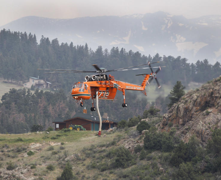 A Erickson Air Crane firefighting helicopter flys to a pond to refill its tank while fighting the High Park wildfire, west of Fort Collins, Colo., on Friday, June 15, 2012. The wildfire started Saturday and has burned over 50,000 acres. (AP Photo/Ed Andrieski)