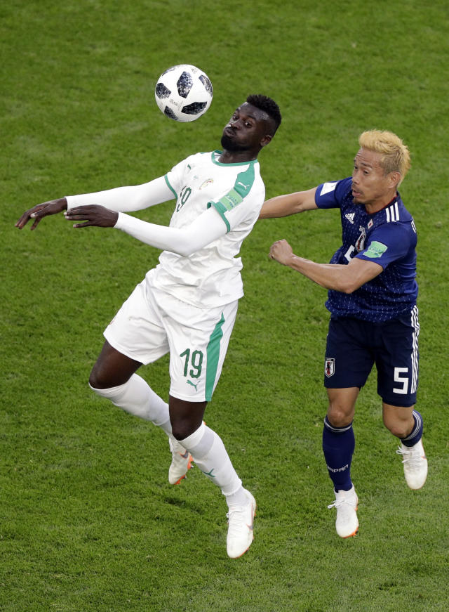 Senegal's Mbaye Niang, left, tussles for the ball with Japan's Yuto Nagatomo during the group H match between Japan and Senegal at the 2018 soccer World Cup at the Yekaterinburg Arena in Yekaterinburg , Russia, Sunday, June 24, 2018. (AP Photo/Mark Baker )